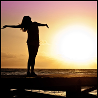 lady on dock with background ocean and sun image